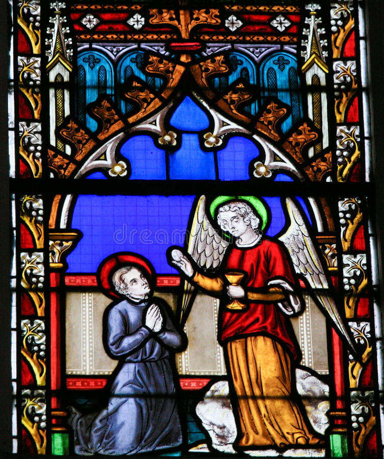 Stained Glass - Angel giving Holy Communion. Stained Glass window in the Church of Braine-le-Chateau, Wallonia, Belgium, depicting an Angel giving sacramental stock photography