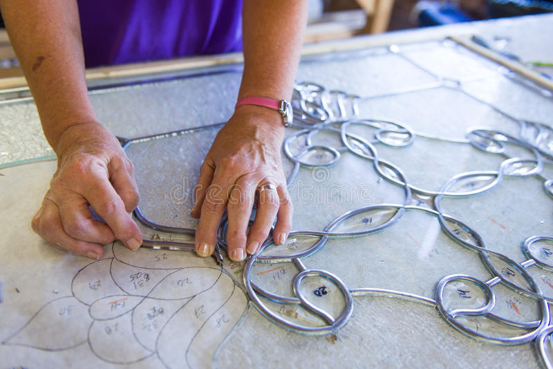 Stained Glass Artisan. A stained glass artisan designs and lays out a new window stock photos