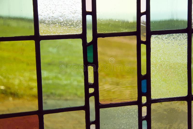 Stained glass background. Vibrant colours of countryside outside through thick stained glass in traditional building stock image
