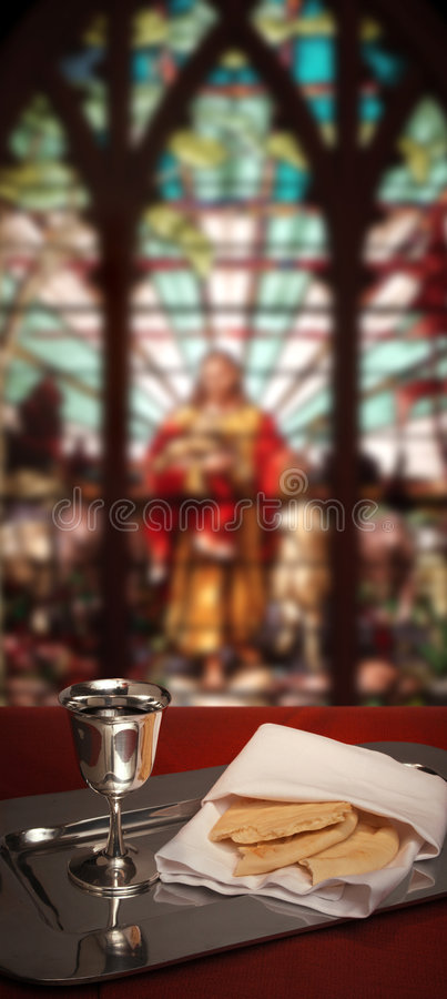 Stained glass communion. Communion chalice and bread with stained glass window in the background stock photography