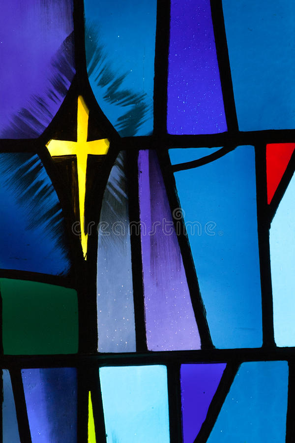 Stained Glass Cross. A blue and purple stained glass window is the perfect background to lead the viewer's eye to the bright yellow cross. This image is a stock photos