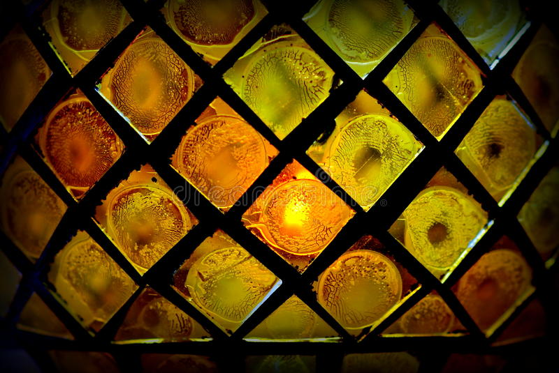 Stained glass. Detail of a yellow coloured stained glass candle holder royalty free stock photos