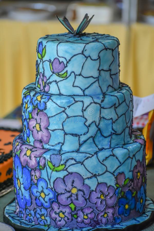 Stained Glass, Floral, Decorated Cake. A three tiered, decorated cake, made to have the appearance of stained glass with blue and purple flowers with yellow stock images