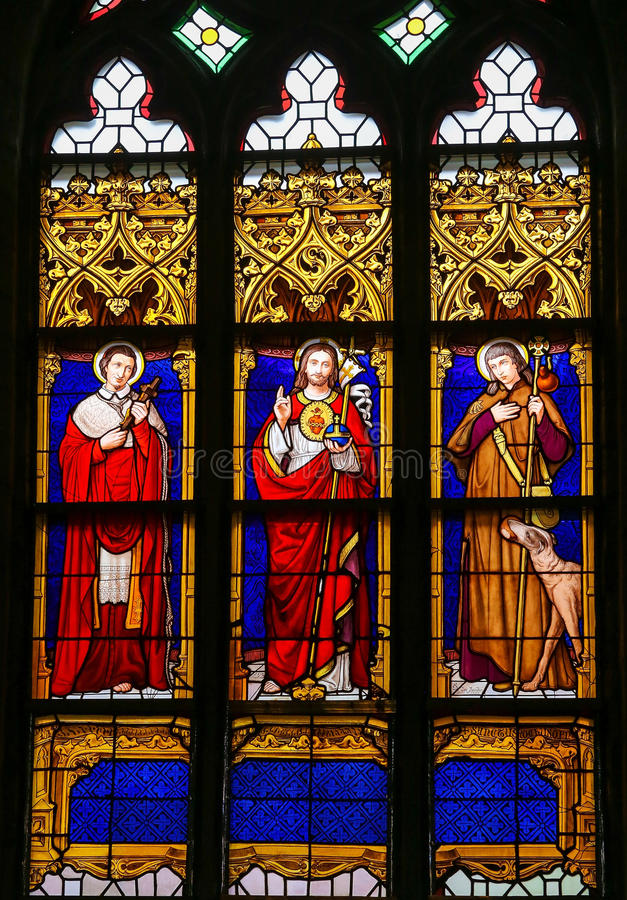 Stained Glass - Jesus Christ, Saint Roch and Saint Charles Borromeo. Stained Glass window in the 15th Century Elzenveld Chapel in Antwerp, Belgium, depicting stock photos