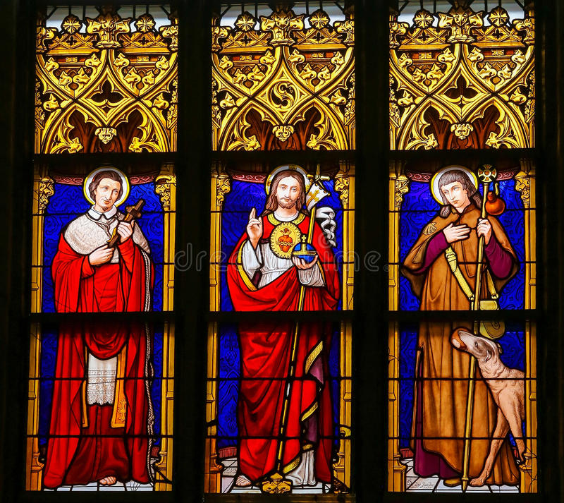 Stained Glass - Jesus Christ, Saint Roch and Saint Charles Borromeo. Stained Glass window in the 15th Century Elzenveld Chapel in Antwerp, Belgium, depicting stock photo