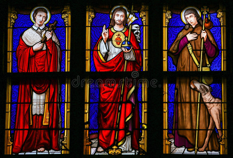 Stained Glass - Jesus Christ, Saint Roch and Saint Charles Borromeo. Stained Glass window in the 15th Century Elzenveld Chapel in Antwerp, Belgium, depicting royalty free stock photos