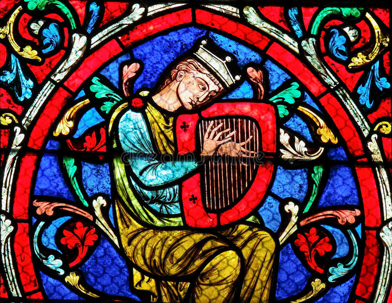Stained glass in Notre Dame Cathedral, Paris - King David. Stained glass window in the Notre Dame Cathedral in Paris, depicting King David playing on his Harp stock image