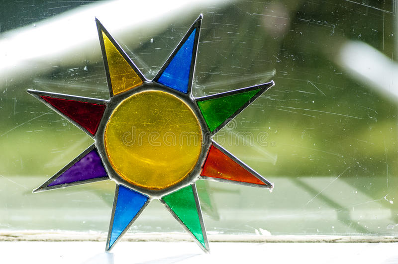 Stained glass ornament. Small stained glass ornamentaal star by a window royalty free stock photography