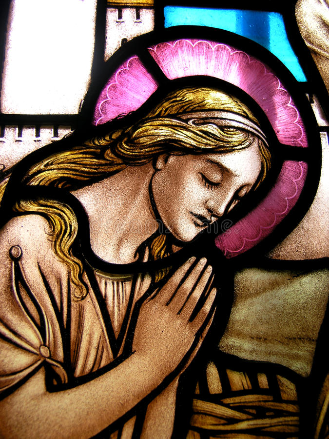 Stained glass prayer. A shot of a stained glass window showing a woman praying stock images