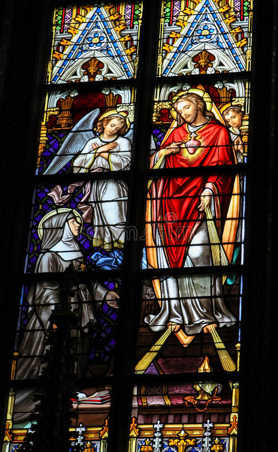 Stained Glass of Sacred Heart of Jesus in Den Bosch Cathedral. Stained Glass Window depicting Saint Lutgardis in adoration to the Sacred Heart of Christ in Den royalty free stock photos