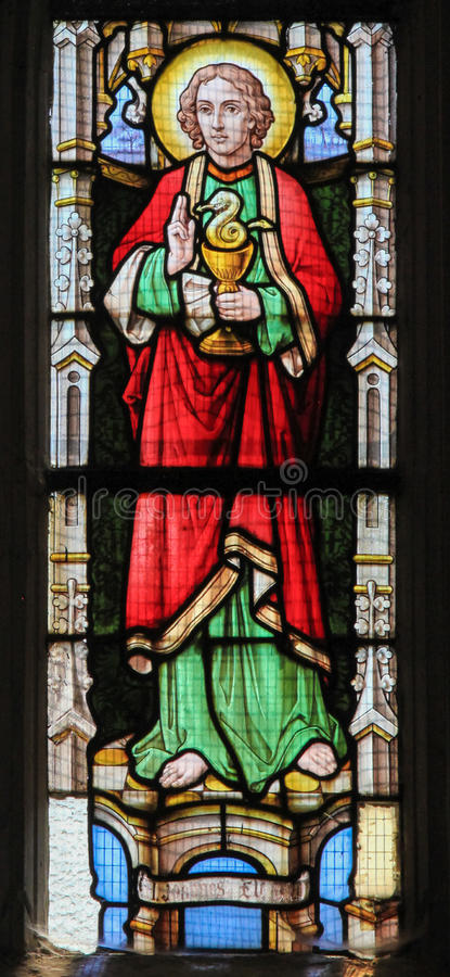 Stained Glass - Saint John the Evangelist. Stained glass window depicting Saint John the Evangelist, holding a cup with a snake, in the Church of Stabroek royalty free stock photo