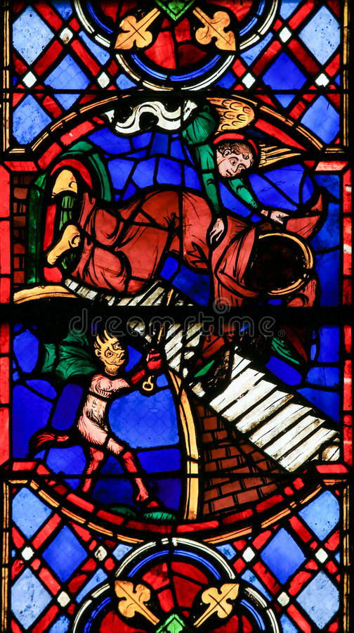 Stained Glass in Tours Cathedral - Good and Evil. Stained glass window depicting a Devil and an Angel fighting for the soul of a monk in the Cathedral of Tours stock images