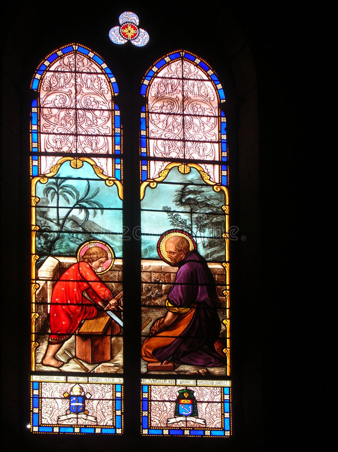 Stained glass window. A stained glass window of Joseph and baby Jesus working wood royalty free stock photography