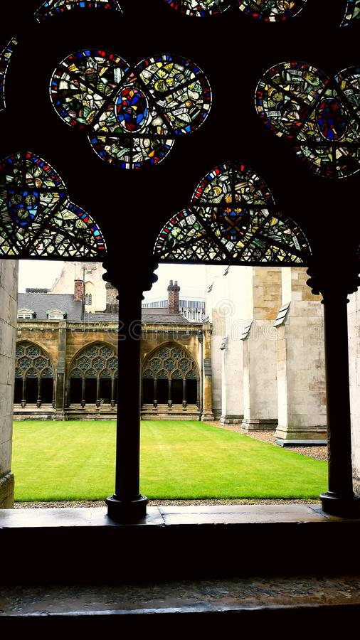 Stained glass window of ancient church overlooking green grass of courtyard. Stained glass window of ancient church Westminster Abbey overlooking green grass of royalty free stock photos