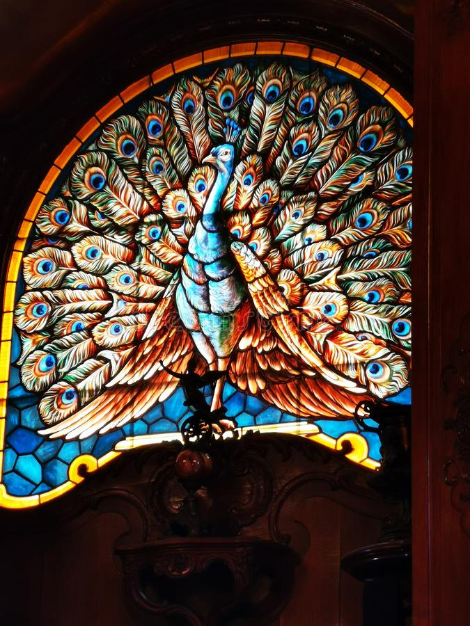 Stained glass window at Cantacuzino Palace interior. And solid wood sculpture royalty free stock image