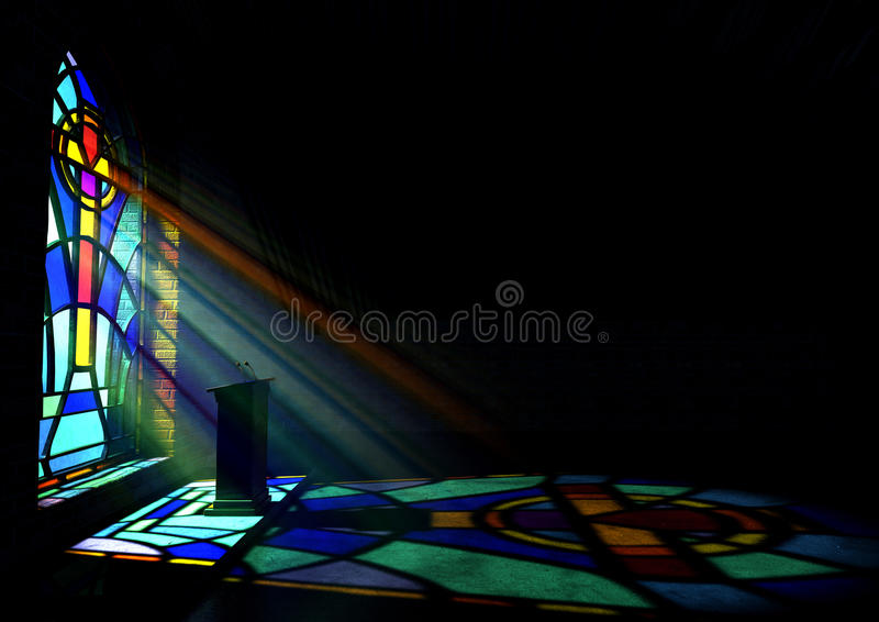 Stained Glass Window Church. A dim old church interior lit by suns rays penetrating through a colorful stained glass window in the pattern of a crucifix stock photo