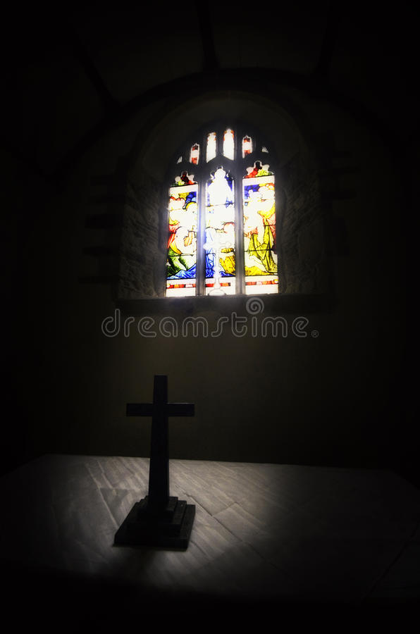Stained glass window in church. Light shining through stained glass window in church silhouetting cross in foreground royalty free stock images