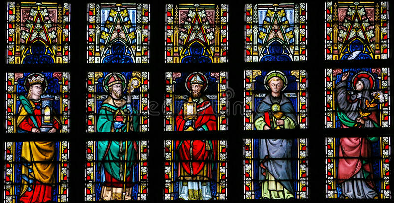 Stained glass window depicting Catholic Saints. Including Saint Barbara, Saint Thomas of Aquino and Saint Norbertus, in the Cathedral of Saint Truiden in stock photos