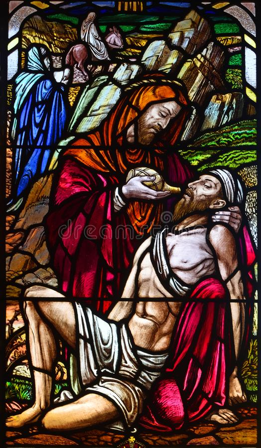 Stained Glass Window Depicting the Good Samaritan in Roxton Chapel. ROXTON, BEDFORDSHIRE, ENGLAND - JUNE 30, 2018: Stained Glass Window Depicting the Good royalty free stock photo