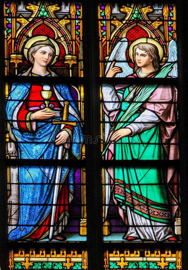 Stained Glass of Saint Barbara and an angel in Den Bosch Cathedr. Stained Glass Window depicting Saint Barbara with tower, sword, chalice and Eucharist and an royalty free stock photography