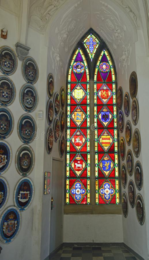 Stained Glass window with heraldic crests - The Chapel Interior - Frederiksborg Castle. Stained Glass Window with heraldic crests in The ornate and beautiful stock photography