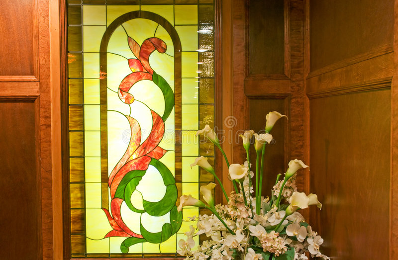 Stained glass window and plant. A view of a beautiful, decorative stained glass window near a flowering plant in the corner of a wood-paneled room stock image