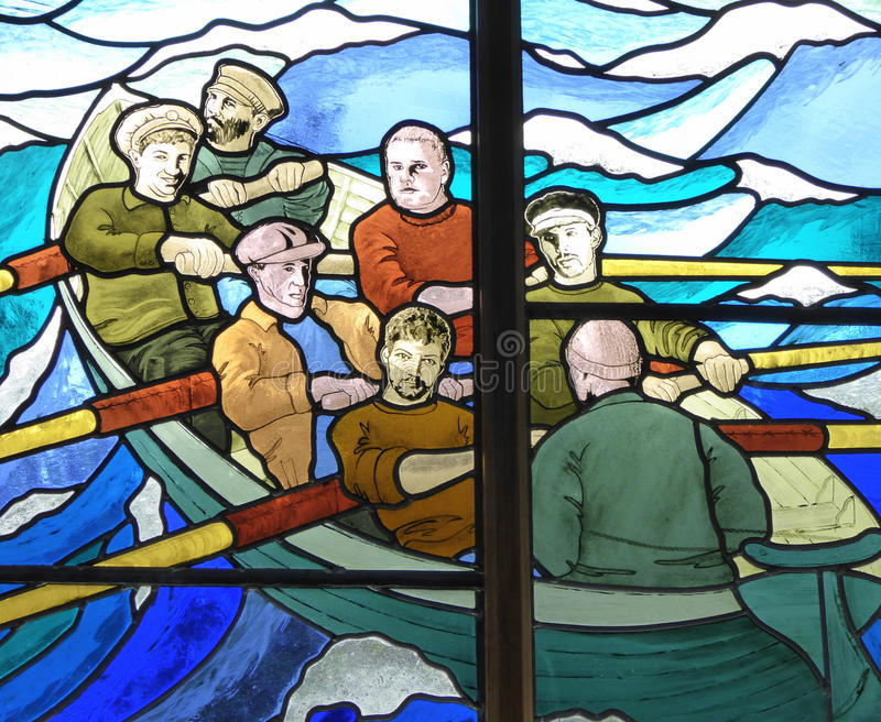 Stained glass picture of men in rowing boat. A stained glass window in Saint Agnes church on Saint Agnes island Isles of Scilly, England stock photos
