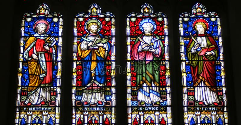 Stained glass windows in English church. Stained glass windows depicting the four evangelists Matthew Mark Luke John in a church in England stock photos