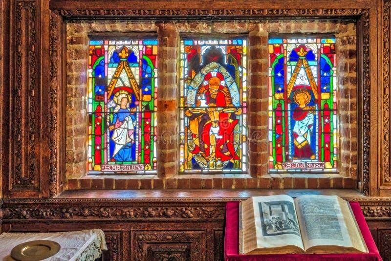 Stained glass windows in Hever Castle. Hever Castle, England - April 2017 : Stained glass windows in a chapel inside Hever Castle, historical home of Ann Boleyn stock photos