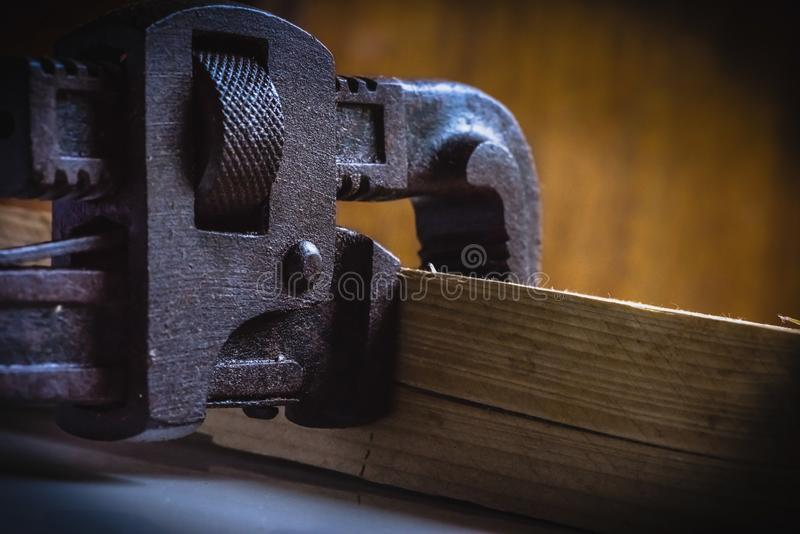 Stained Pipe Wrench handtool with wooden block. Rusted, stained pipe wrench hand tool clamped with a wooden block royalty free stock photography