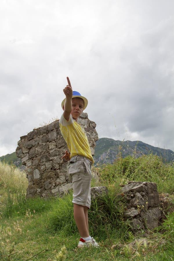 staing在S古老堡垒的废墟的附近一个蓝色帽子的男孩  库存图片