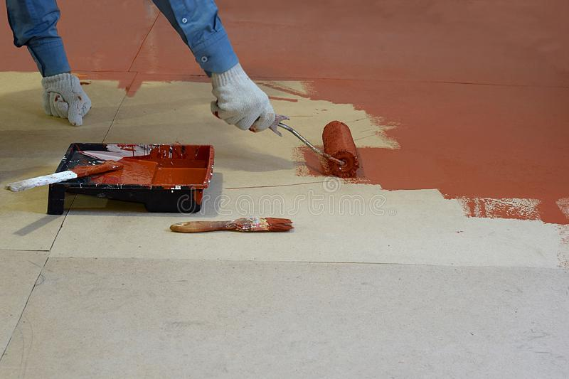Coloring the floor with brown paint. Staining the floor with a brown paint with a roller stock photo