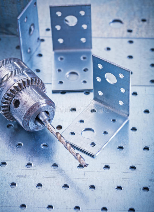 Stainless drilled angle fasteners and metal drill. On perforated metallic sheet construction concept stock images
