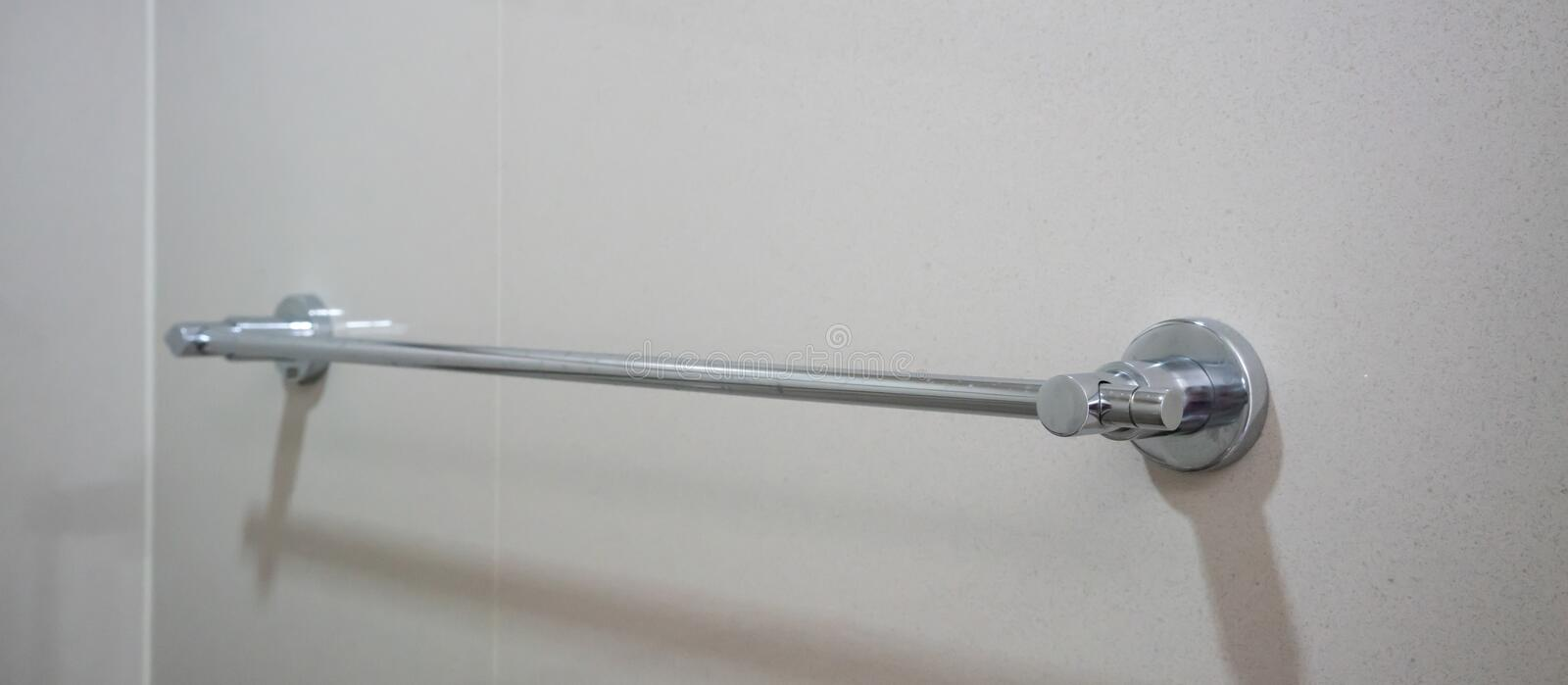 Stainless silver towel rail mounted on grey tile wall. Bathroom accessories detail stock photography
