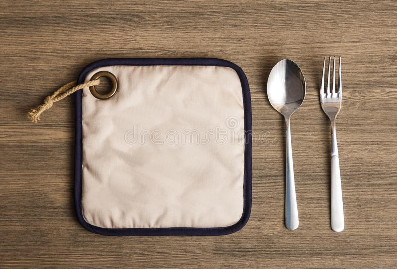 Stainless spoon and fork. Portrait of stainless spoon and fork on wooden table royalty free stock images