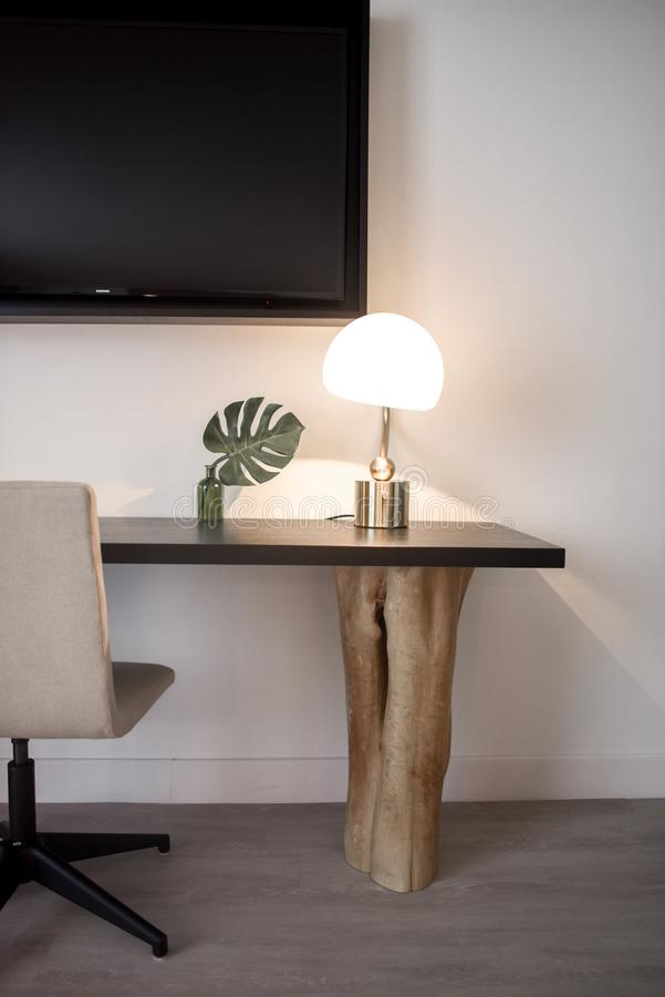 Stainless Steel Base White Shade Table Lamp on Brown Wooden Desk Near White Painted Wall With Wall Mounted Flat Screen T V stock images