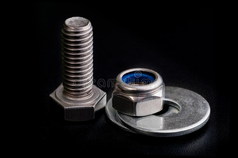 Stainless steel bolt with a nut and washers on black royalty free stock image