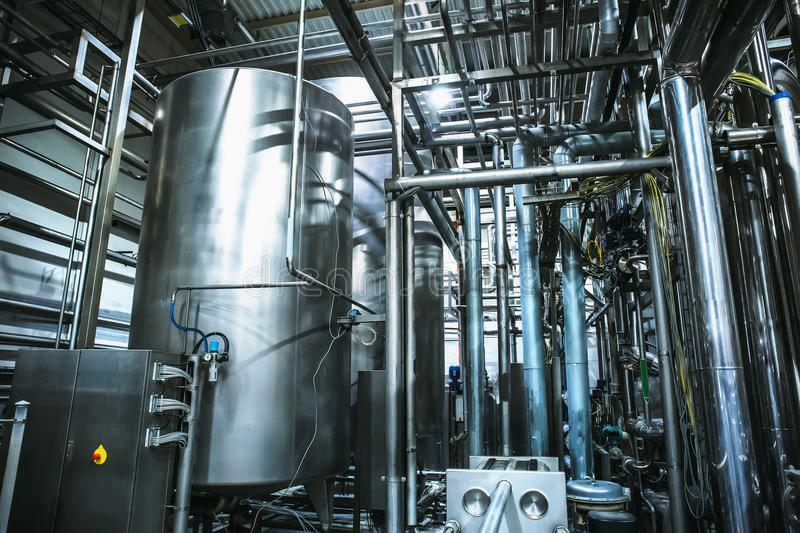 Stainless steel brewing equipment : large reservoirs or tanks and pipes in modern beer factory. Brewery production stock photo