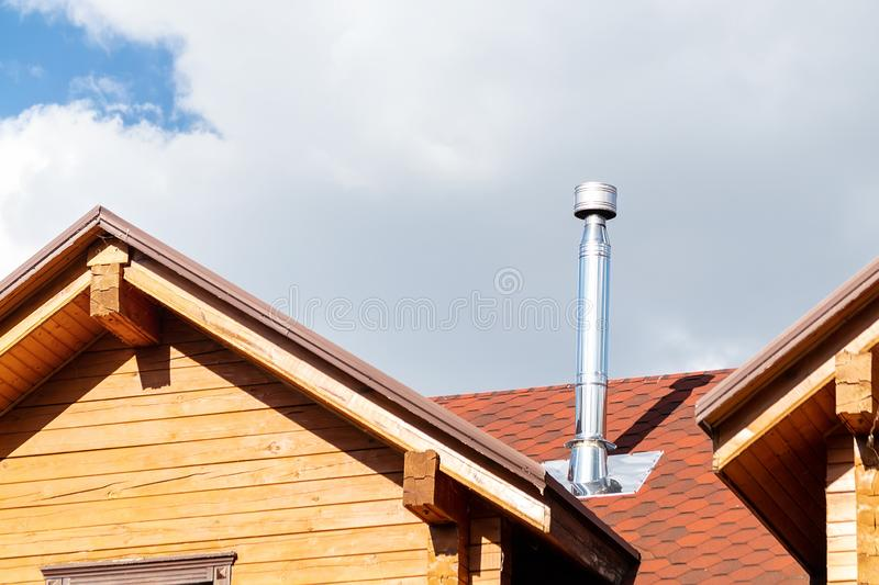 Stainless steel chimney pipe on roof of modern wooden beam cottage villa house. Home fireplace and heating exhaust stock photos