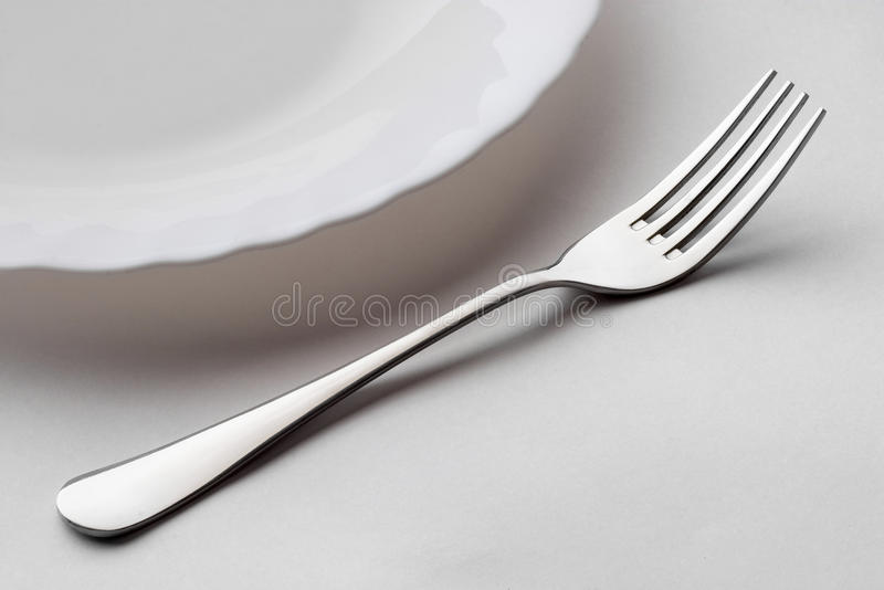 Stainless steel fork. And a fragment of the porcelain plate macro shot royalty free stock images