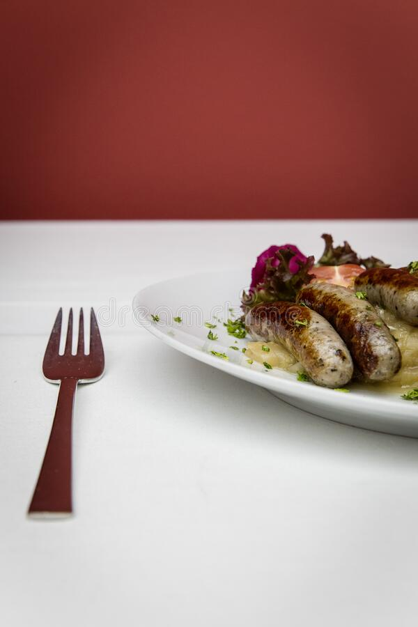 Stainless Steel Fork Near White Ceramic Round Plate With Sausage royalty free stock photography