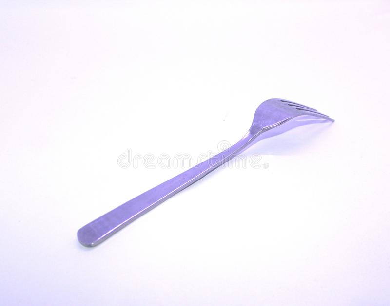 A stainless steel fork in sideways position. In white background stock photos