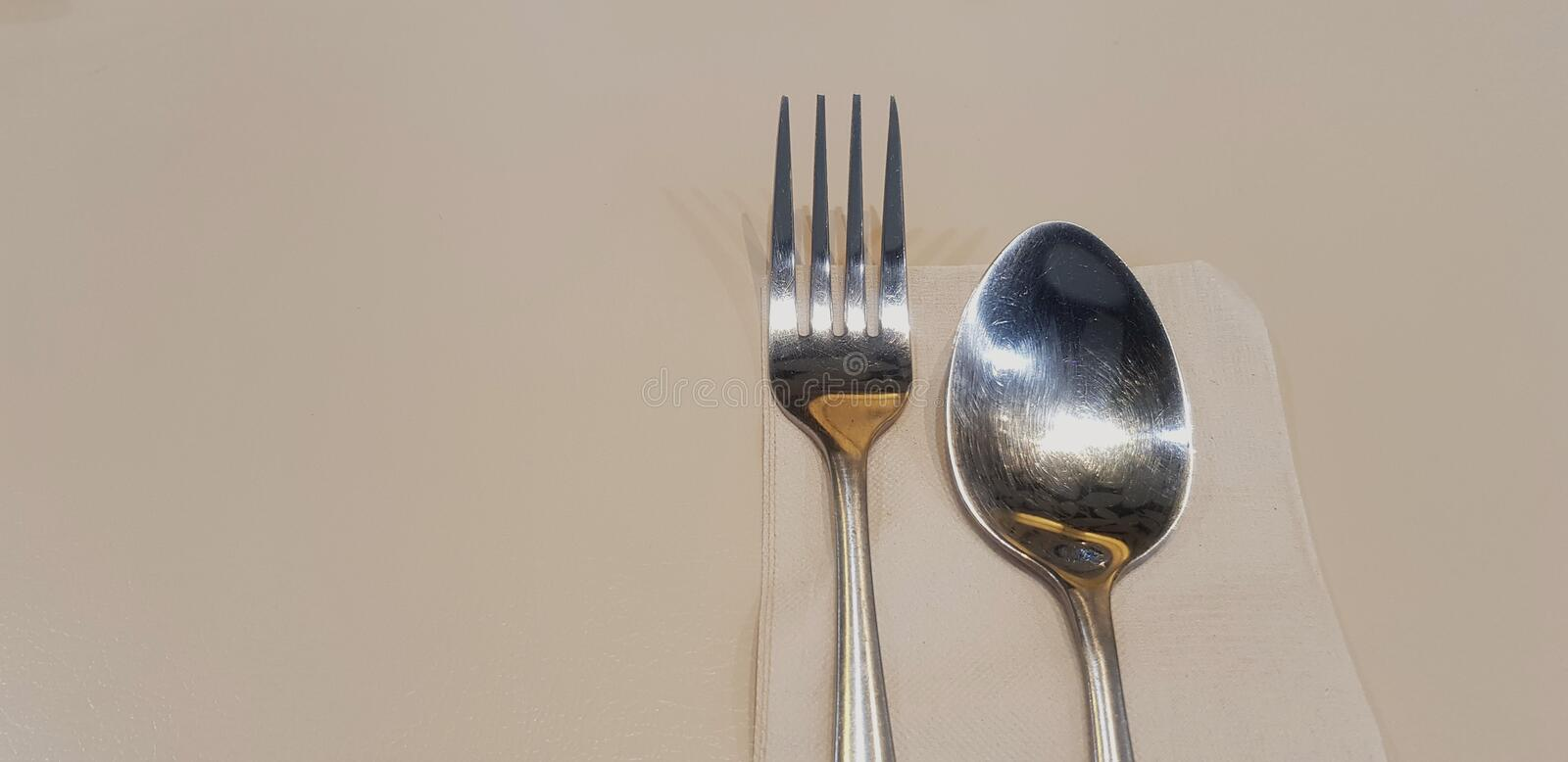 Stainless steel fork and spoon on brown napkin or towel paper setting on dinner table with copy space. Preparation, Utensil, Dining table and Shape of object stock images