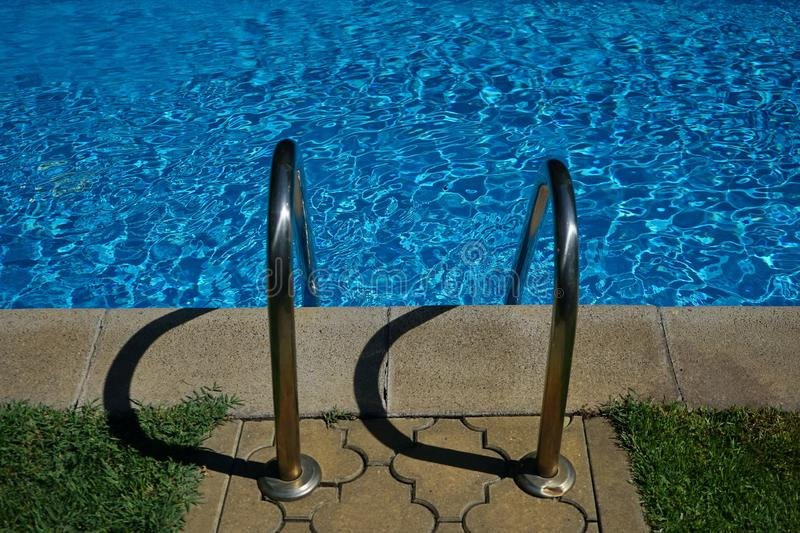 Stainless steel handrail stair of swimming pool with shadows royalty free stock photography