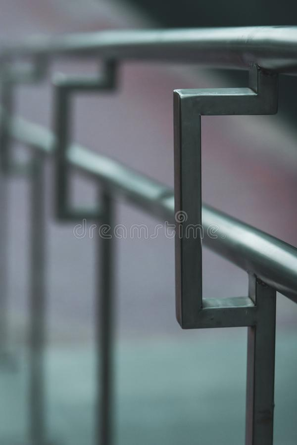 Stainless steel handrails on the street receding into the distance with selective focus. Vertical frame. royalty free stock photography
