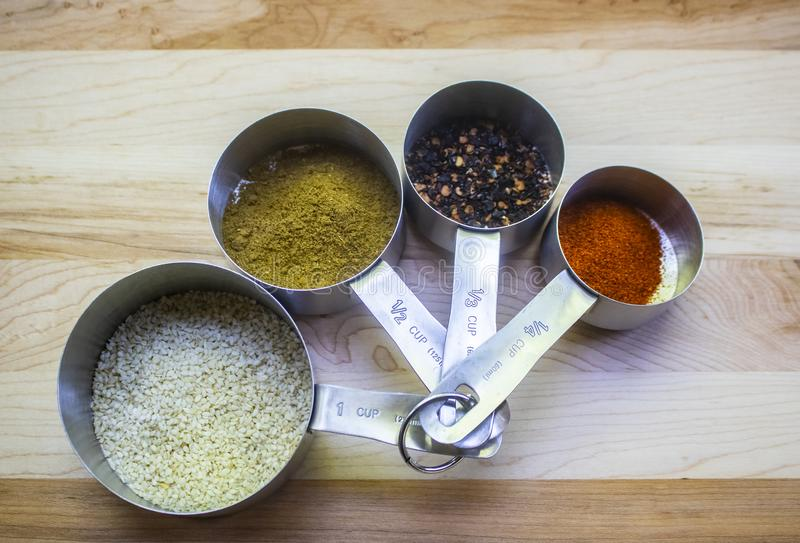 Stainless steel measuring cups holding assorted spices sitting on cutting board stock images