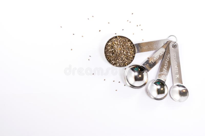 Stainless steel measuring spoons with plant seeds isolated royalty free stock photos
