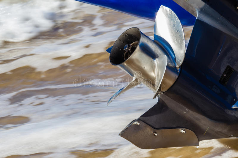 Stainless Steel Prop Outboard Motor. Close up photo image of four blade stainless steel prop on outboard motor for boat with steel plate wrap around gearbox fin stock photography