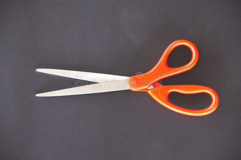 Stainless steel scissors, orange handle royalty free stock photography