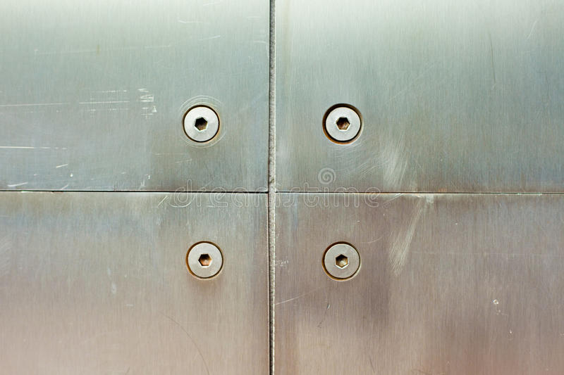 Stainless steel screws and panels. Stainless steel screws holding brushed steel panel on wall of modern building stock images
